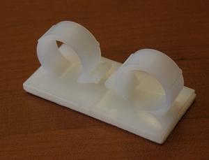 Adhesive nylon clip 28,5x28,5x23mm, fix Ø18-21mm<br />Price per piece